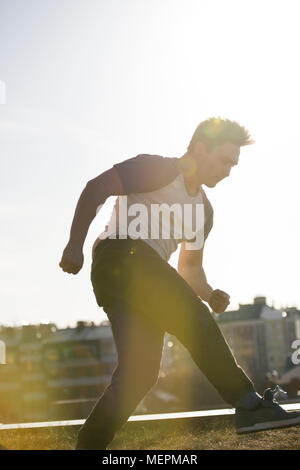 Jeune homme sportif parkour effectue des sauts acrobatiques devant skyline Banque D'Images