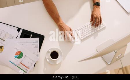 Vue de dessus d'un homme travaillant sur ordinateur avec des documents et une tasse de café sur la table. L'homme à l'aide d'un clavier et une souris sans fil tout en travaillant sur l'ordinateur Banque D'Images