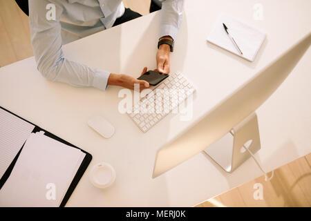 Vue de dessus d'un homme à l'aide de téléphone mobile assis en face de l'ordinateur avec des documents et du café sur la table en verre. L'homme à l'aide du clavier et de la souris sans fil Banque D'Images