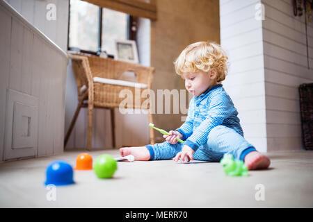 Bébé garçon avec une brosse à dents assis sur le plancher dans la salle de bains. Banque D'Images