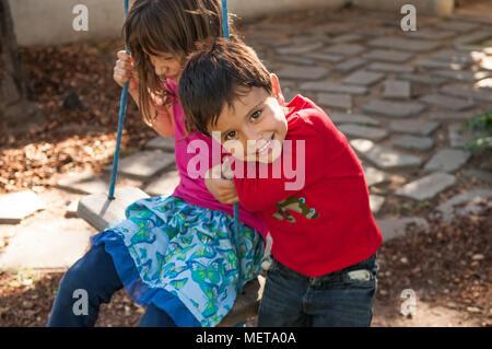 Frère et sœur jouant, la jeune fille est assise sur une balançoire alors que son plus jeune frère ludique sourit à la caméra. Un joli portrait de l'enfant de vie. Banque D'Images
