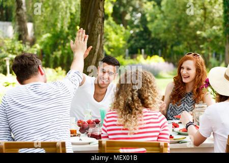 Smiling groupe de jeunes gens s'amuser, rire et manger des aliments sains à l'extérieur Banque D'Images