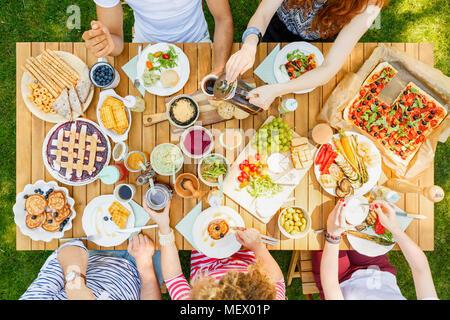Repas en plein air pour les amis de pizza, des fruits, les biscuits, les tartes, les épices et le pain dans le jardin Banque D'Images