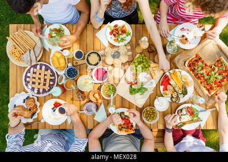 Groupe d'étudiants à un pique-nique de manger des pizzas, tartes, légumes et fruits dans le jardin Banque D'Images
