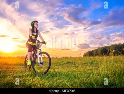 Jeune femme sportive au coucher du soleil sur une bicyclette. Fille sportive en vélo à l'arrêt pour profiter de l'instant du beau coucher du soleil. Lens flare contre le fond de ciel Banque D'Images