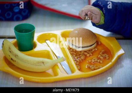 Un déjeuner scolaire plateau à repas avec burger, les haricots, les fruits et les boissons de la banane Banque D'Images