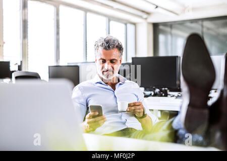 Relaxed mature businessman sitting at desk in office using cell phone et de boire du café Banque D'Images