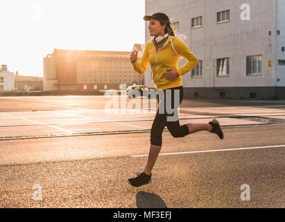 Jeune femme tournant sur une rue au coucher du soleil Banque D'Images