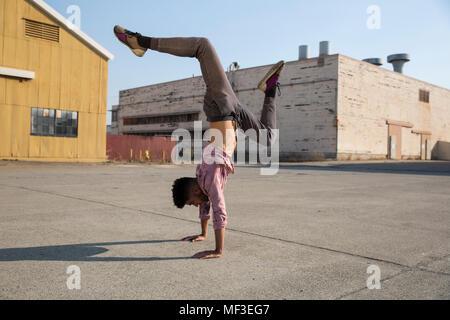 Jeune homme faisant un handstand outdoors Banque D'Images