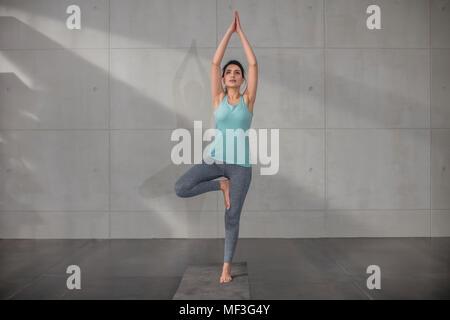 Young woman doing yoga exercice en studio Banque D'Images