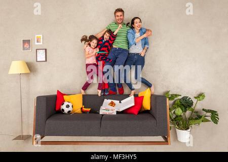 Famille heureuse avec deux enfants regarder le football dans la salle de séjour Banque D'Images