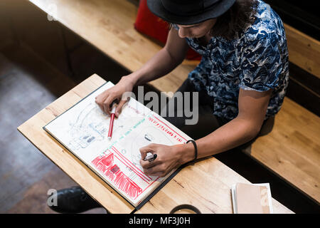 Artiste assis dans un café, dans son carnet de dessin Banque D'Images