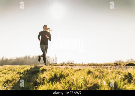 Jeune femme tournant sur chemin rural Banque D'Images