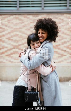 Espagne, Barcelona, two happy women embracing dans la ville Banque D'Images