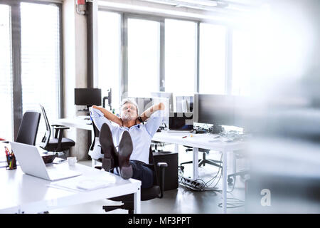 Relaxed mature businessman sitting at desk in office penché en arrière Banque D'Images