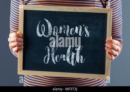 Les mains tenant petit tableau noir à l'avant du corps avec un texte indiquant que la santé des femmes Banque D'Images