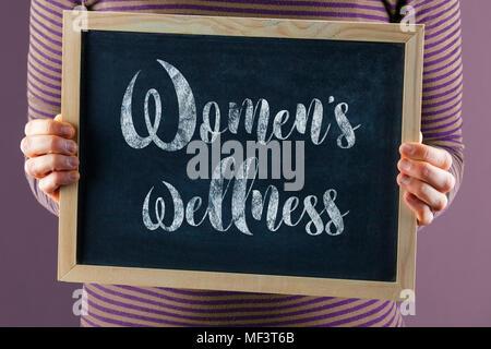Les mains tenant petit tableau noir à l'avant du corps avec un texte indiquant que le bien-être des femmes Banque D'Images
