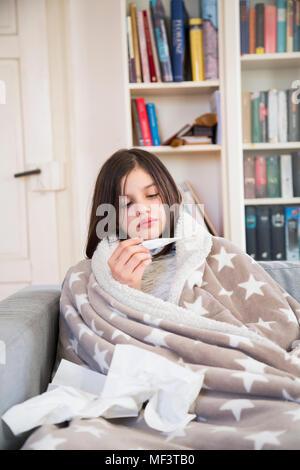 Sick girl assis sur le canapé à la maison à la recherche clinique au thermomètre Banque D'Images