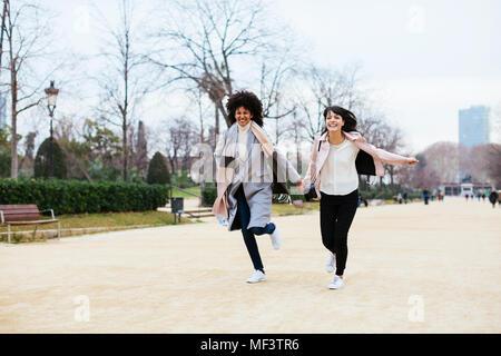 Espagne, Barcelone, deux femmes exubérantes s'exécutant dans city park Banque D'Images