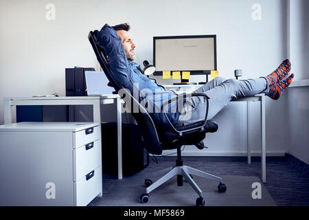 Man sitting at desk in office relaxing Banque D'Images