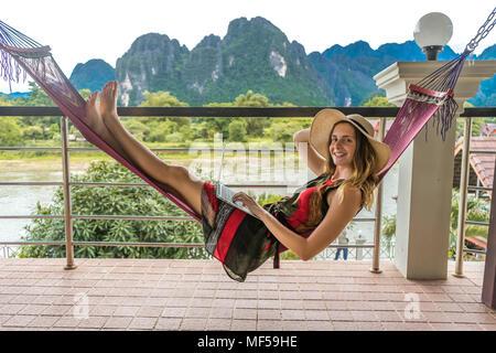 Le Laos, Vang Vieng, woman lying in hammock, using laptop