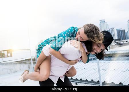 Young affectionate couple s'amuser ensemble sur le toit Banque D'Images