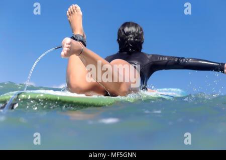 L'INDONÉSIE, Bali, femme surfer allongé sur une planche de surf Banque D'Images