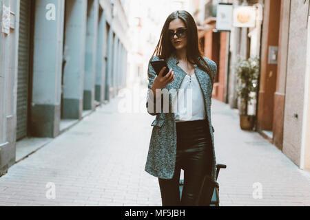 Young businesswoman dans la ville contrôle cell phone Banque D'Images