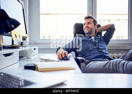 Ambiance man sitting at desk in office looking at computer screen Banque D'Images