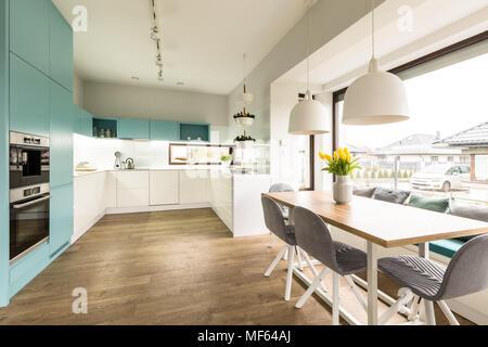 Cuisine intérieur blanc et bleu avec grande table à manger, chaises et fenêtre Banque D'Images