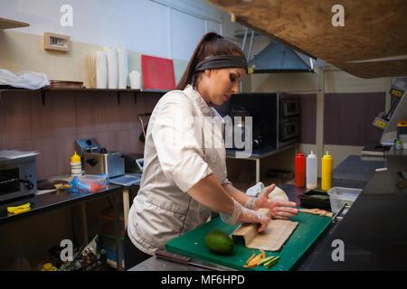 Femme en blanc chef prépare restaurant sushi Banque D'Images