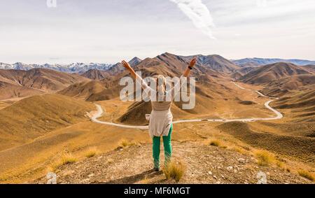 Femme regardant stark mountain landscape with mountain road, Lindis Pass, Alpes du Sud, de l'Otago, Southland, Nouvelle-Zélande Banque D'Images