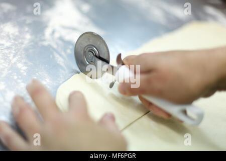 Couper une pâte feuilletée avec un couteau à pizza sur une table en acier. Haut les mains et la pâte a close-up de la farine sur la table. Banque D'Images