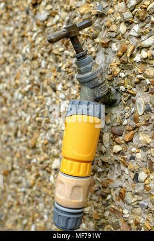 Près d'un robinet extérieur attaché à un mur en pointillés de galets. Banque D'Images