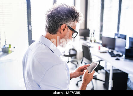 Mature businessman in office using smartphone Banque D'Images
