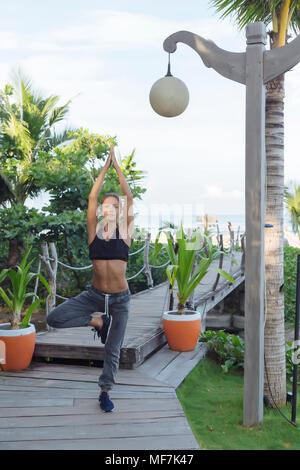 L'INDONÉSIE, Bali, woman practicing yoga, position d'arbre Banque D'Images