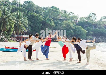 La Thaïlande, Koh Phangan, groupe de personnes faisant du yoga sur une plage Banque D'Images