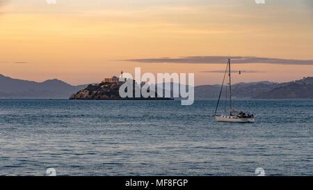 Un voilier passe par l'île d'Alcatraz à San Francisco Bay au crépuscule
