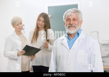 Certains vieux médecin restant en face de assistant et patient. À expirienced, qualifiés, professionnels. Travaillant en laboratoire d'ophtalmologie vision gor sauver et d'améliorer. Banque D'Images