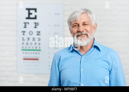 Ancien patient restant en face de l'inspection visuelle tableau accroché sur mur blanc en laboratoire d'ophtalmologie. Homme portant une chemise bleue et une barbe. Essayer d'améliorer la vision de la santé de l'œil. Banque D'Images