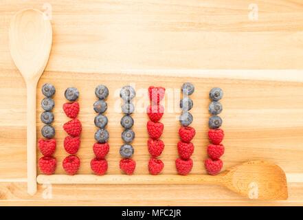 Graphique statistique faite de cuillères de cuisine, bleuets et framboises fraîches sur une planche à découper en bois brun Banque D'Images