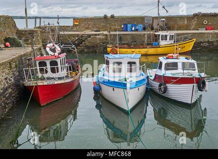 Quatre bateaux de pêche locaux irlandais colorés amarrés jusqu'à marée basse dans le port de Fethard dans le comté de Wexford, Irlande du Sud. Banque D'Images