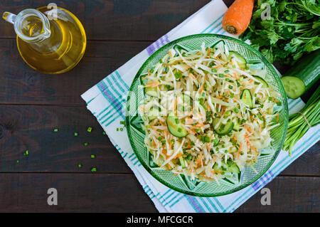Salade diététique avec du chou, concombre, carotte, légumes verts. Salade de printemps juteux avec légumes frais sur une table en bois. Une bonne nutrition. Banque D'Images