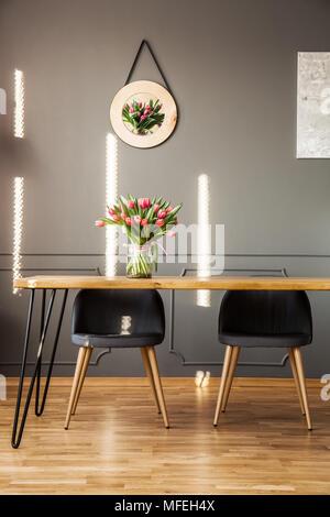 Chaises gris à table en bois avec des fleurs à l'intérieur salle à manger au décor sur le mur