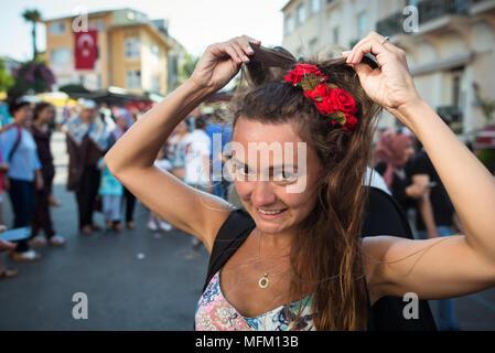 Jeune femme drôle avec des roses dans les cheveux se tient sur la place de la ville et corrige la coiffure. Confus fille sur fond de groupe de personnes.