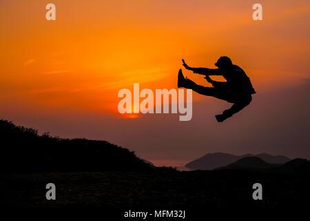 Silhouette de jeune homme sautant avec ciel crépusculaire. Banque D'Images