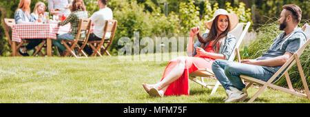 Happy woman relaxing with a friend sur les chaises longues au cours de journée ensoleillée en été Banque D'Images