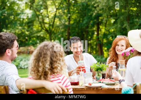 Les jeunes gens rire, manger et parler dans une journée ensoleillée dans le jardin Banque D'Images