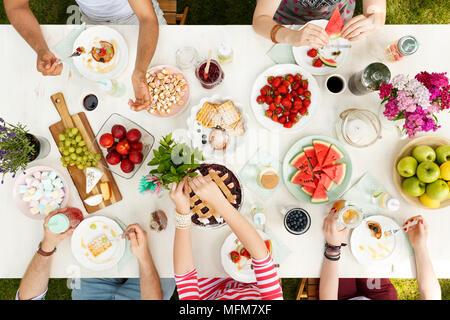 Les jeunes le partage de la nourriture dans le jardin en mangeant des fruits, tarte, fromage avec des fleurs et des bougies sur la table Banque D'Images