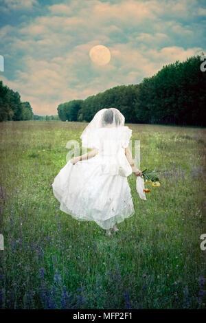 Une femme s'exécute avec une robe de mariage sur un champ de fleurs Banque D'Images